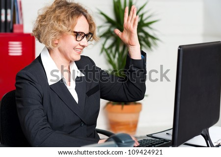 Smiling woman with raised arm looking at screen and typing on keyboard with other hand