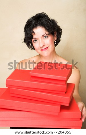 Smiling woman with short curly hair, holding a stack of red gift boxes