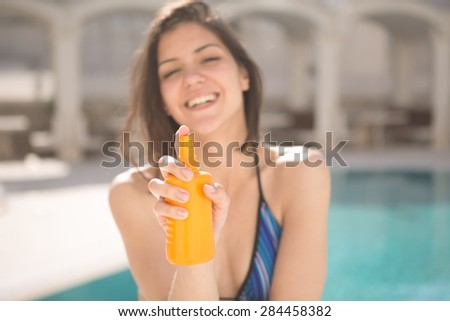Smiling woman with sun creme.Young beautiful cheerful tanned woman with sun UV  high SPF protection cream.Sunscreen.Sunblock.Woman showing solar cream by the pool on sunny summer day.Focus on cream