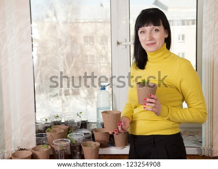 Smiling woman with various seedlings at home