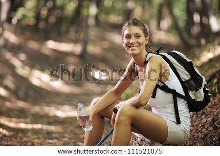 Smiling woman with walking sticks in a forest, having a break