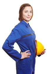 Smiling woman worker in blue overall and helmet