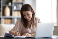 Smiling woman writing notes in notebook daily planner, planning week, working or studying at home, using laptop, beautiful female wearing wireless earphones listening to music or lecture
