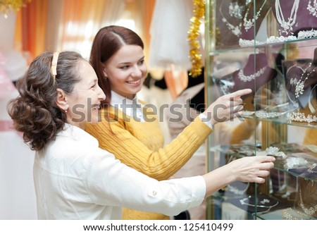 Smiling women  chooses bridal accessories at store of wedding fashion