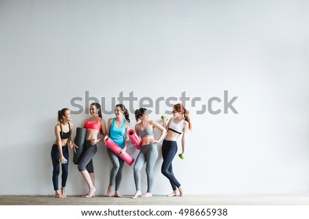 Smiling women in fitness studio. Fitness, sport, training and lifestyle concept.