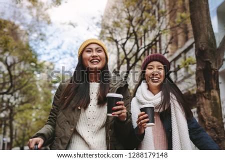 Smiling women in winter wear walking on street drinking coffee. Asian tourist women walking around the city on a winter morning. Stock fotó ©