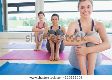 Smiling women sitting on yoga mats in fitness studio