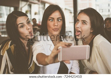 Smiling women taking selfie together outdoors. Girls making funny face.