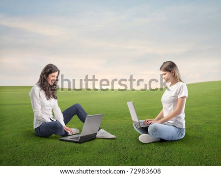 Smiling women using laptops on a green meadow