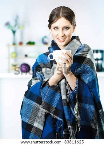 smiling women with blanket wrapped around in kitchen
