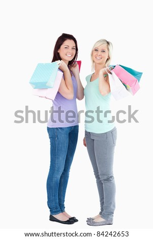 Smiling women with shopping bags in a studio