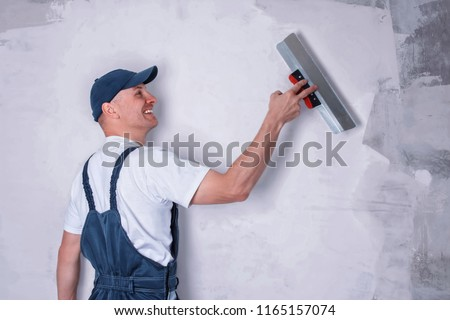 Smiling worker in profile wearing overalls and cap plastering a wall with finishing putty using a putty knife. Repair work and construction concept
