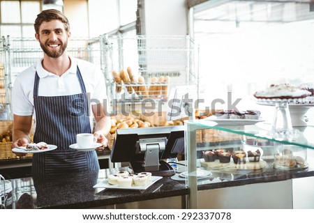 Smiling worker prepares breakfast at the bakery