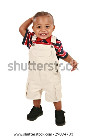 Smiling 1-year old baby boy standing facing camera on isolated background