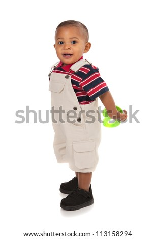 Smiling 1-year old baby boy standing Full Body Length Portrait holding toy on isolated background