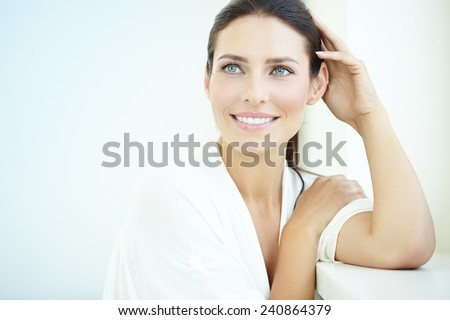 Shutterstock Smiling 30 year old woman at the window. Fresh light blue background.