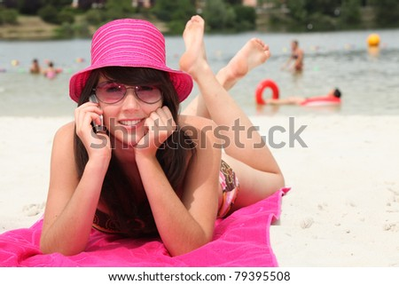 smiling 20 years old Asian girl relaxing on the beach and calling