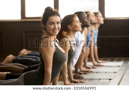 Smiling yoga instructor looking at camera doing fitness stretching backbend exercise together teaching multi-ethnic diverse people at group training class in studio, sporty yogi fit teacher portrait
