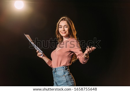 smiling young actress with screenplay on black