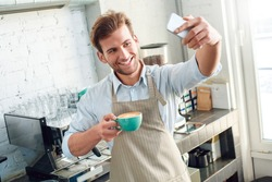 Smiling young adult barista in apron working in coffeeshop, standing near professional coffee machine, making selfie photo with cup of beverage