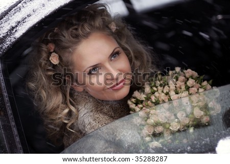 Smiling young adult bride holding bouquet of flowers looking out of limousine window on snowy, wintry day. - stock photo
