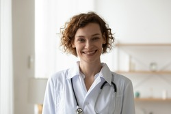 Smiling young adult woman doctor wearing white medical coat and stethoscope head shot close up portrait. Happy female physician, therapist, general practitioner looking at camera standing in hospital.