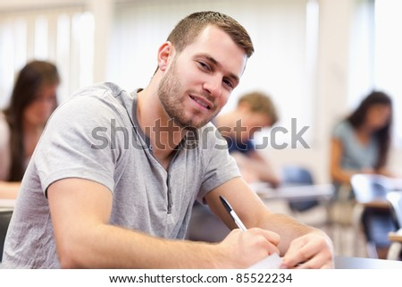 Smiling young adult writing in a classroom