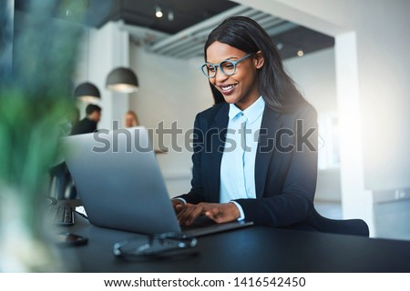 Smiling young African American businesswoman working online with a laptop while sitting at her desk in a bright modern office