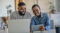 Smiling young African American couple sitting together at their dining table using a laptop and a digital tablet to work out their household finances