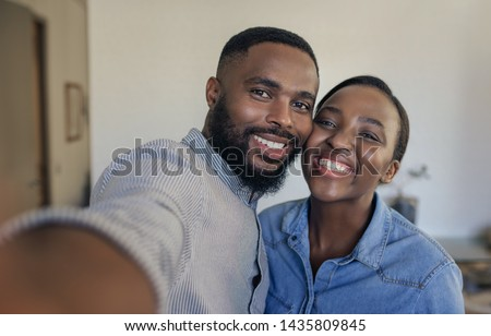 Smiling young African American couple standing in their living room at home taking selfies together