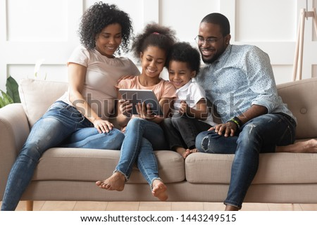 Smiling young african American family sit on couch with little kids watch cartoons on tablet, happy black parents have fun relax with children on sofa enjoy video on pad spending time at home together stock photo
