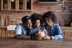 Smiling young African American family with daughter save money in piggybank feel provident economical about finances. Happy biracial parents with ethnic child make financial investment for future.