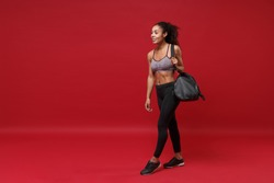 Smiling young african american fitness woman in sportswear posing working out isolated on red background. Sport exercises healthy lifestyle concept. Holding sports bag with equipment, looking aside