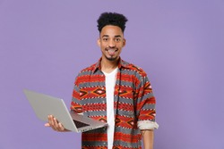 Smiling young african american guy in casual colorful shirt posing isolated on violet background studio portrait. People emotions lifestyle concept. Mock up copy space. Working on laptop pc computer