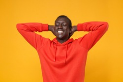 Smiling young african american man guy in red streetwear hoodie posing isolated on yellow orange background. People lifestyle concept. Mock up copy space. Relaxing, sleeping with hands behind head