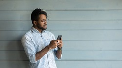Smiling young african american man in eyewear using mobile applications, involved in distant communication with friends, online shopping or web surfing, isolated on wall, copy space for ad text.