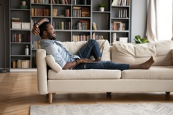 Smiling young African American man relax on comfortable couch in living room using modern laptop, happy millennial biracial male rest on cozy sofa at home working or studying on computer gadget