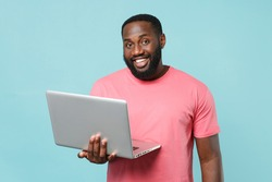 Smiling young african american man 20s in casual pink t-shirt isolated on pastel blue wall background studio portrait. People lifestyle concept. Mock up copy space. Working on laptop pc computer