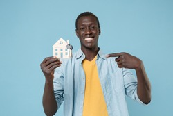Smiling young african american man 20s in casual shirt yellow t-shirt isolated on blue background studio. People lifestyle concept. Mock up copy space. Point index finger on house and bunch of keys