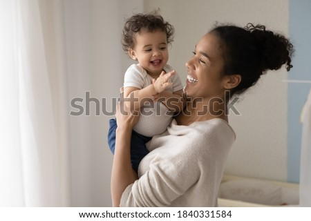 Smiling young african American mom hold in hands happy little ethnic baby infant play at home together. Happy biracial mother hug embrace feel playful with small toddler kid child show love care.