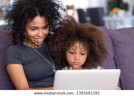 Smiling young African American mom relax with small daughter on couch at home with laptop watching cartoons online, millennial black mommy rest with little child, teach her using computer stock photo