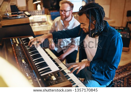 Smiling young African American musican playing keyboards during a session with a producer in a recording studio #1357170845