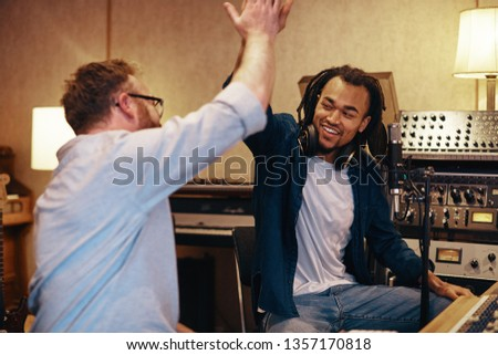 Smiling young African American singer high fiving with his music producer during a studio recording session #1357170818