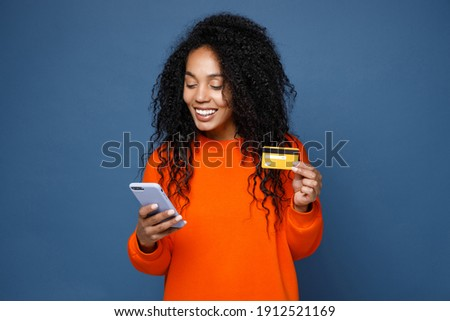 Smiling young african american woman in basic casual bright orange sweatshirt standing using mobile cell phone typing browsing hold credit bank card isolated on blue color background studio portrait