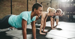 Smiling young African American woman in sportswear doing pushups during an exercise class with a group of friends at the gym