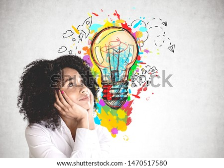Smiling young African American woman in white shirt looking at colorful lightbulb sketch drawn on concrete wall. Concept of good idea