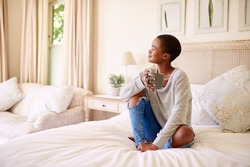 Smiling young African American woman sitting on her bed drinking a cup of coffee and thinking about the day ahead