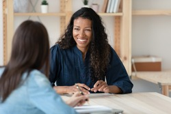 Smiling young African American woman talk with female colleagues brainstorm at office team meeting. Happy multiracial diverse colleagues speak discuss business ideas. Teamwork, collaboration concept.