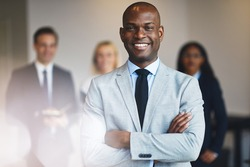 Smiling young African businessman standing with his arms crossed in an office with coworkers standing in the background