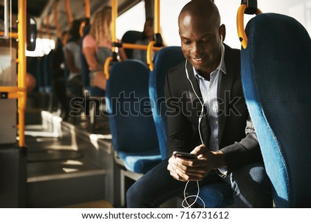 Smiling young African businessman wearing a suit sitting on a bus during his morning commute listening to music on a smartphone and headphones